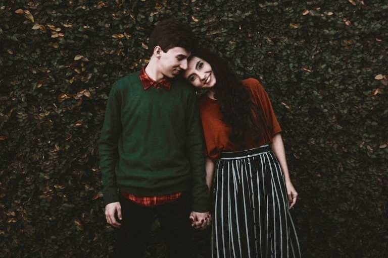 Young cute couple leaning in by hedge