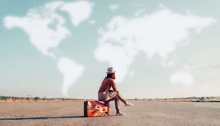 Women Traveler Sitting on case on Airfield, clouds forming map of the world