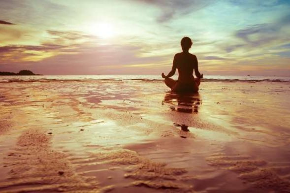 woman meditating on a sunset beach