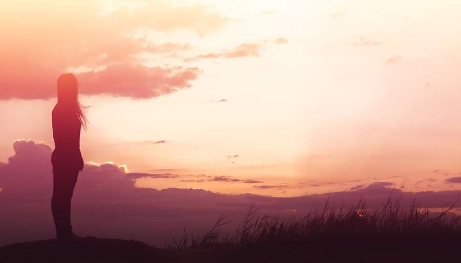 Woman Standing on Clifftop by Beautiful Red Sunset