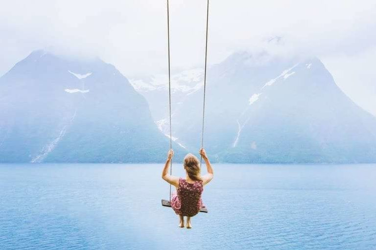 Woman on Sky Swing with Mountains in Distance