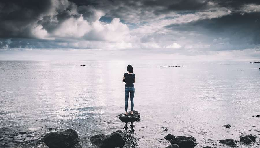 Woman Standing on Empty Beach looking at Horizon