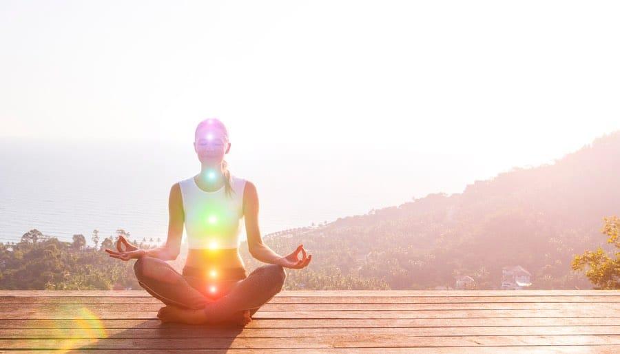 Woman chakra meditation on mountaintop
