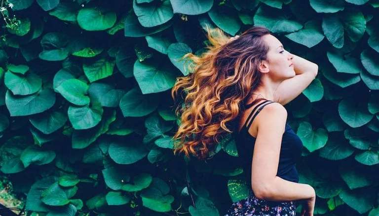 Woman and Leafy Green Wall