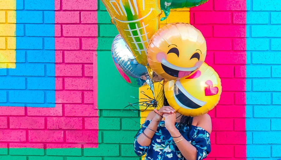 Woman Holding Bright Smiley Face Balloons Leo