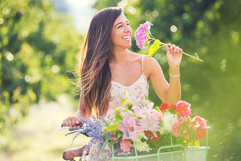 woman on bike smelling flowers