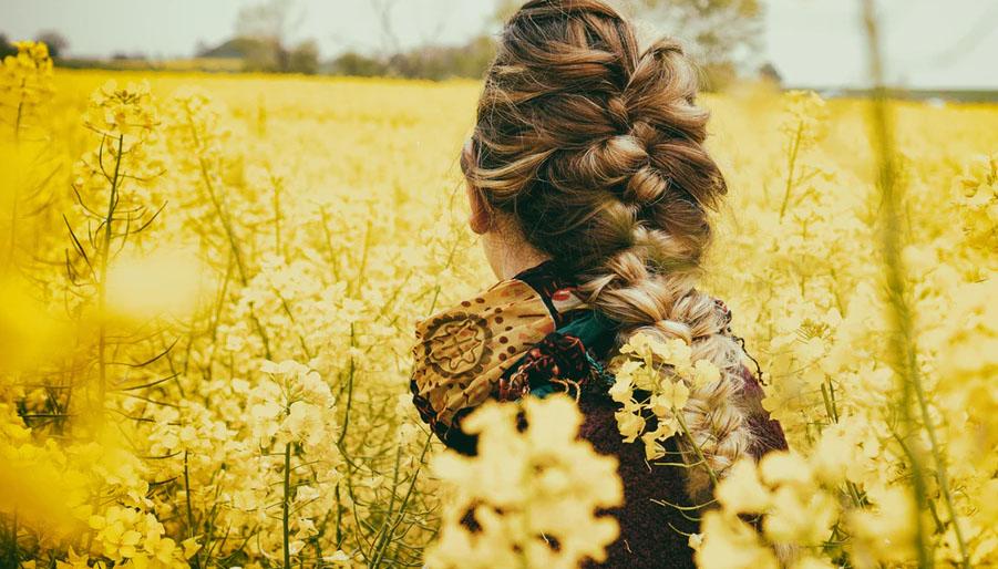virgo woman in a field of yellow flowers