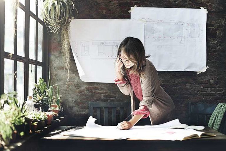Woman drawing plans with many plants around