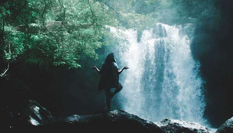 Lady standing peacefully in a zen yoga position with a waterfall cascading in front of her