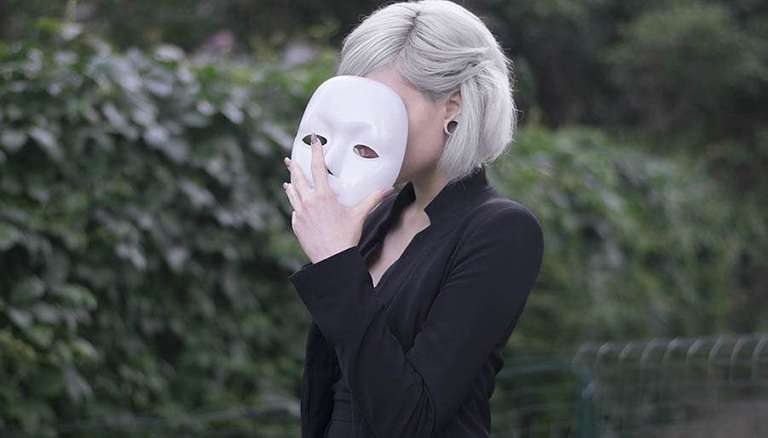 women holding white mask to her face