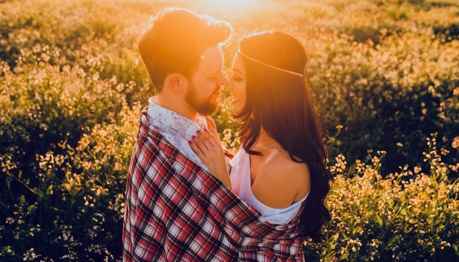Couple Embracing Closely in Sunset Field of yellow flowers